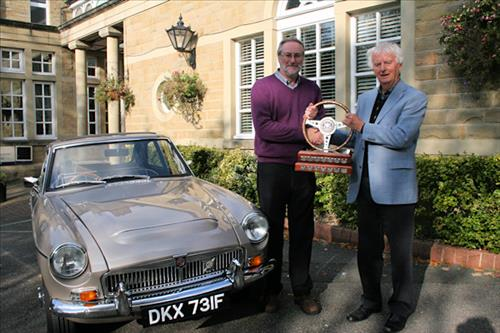The car rally winner receiving his trophy
